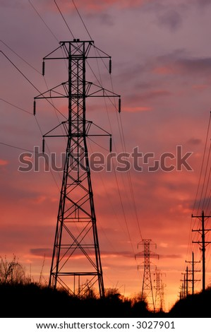 Silhouette power-line tower on sunset