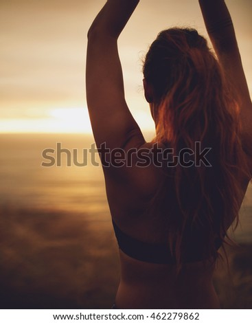 Silhouette rear view of young woman practicing yoga at sunset, doing asana with hands above head.