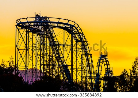 Silhouette roller coaster in the park - stock photo