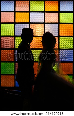 Silhouette romantic Scene of love muslim couples on colorful wall  - stock photo