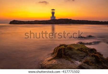 Silhouette sea and sunset at harbor with lighthouse located in the southern province of  Phang Nga in thailand  (focus stone)