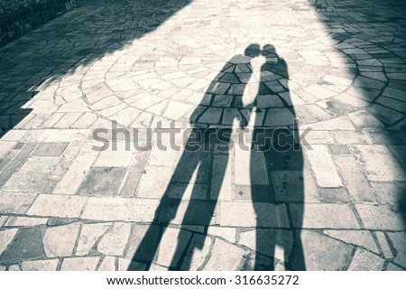 Silhouette shadow of two people holding hands and kissing background, shadow of two adult (girl and boy) holding hands at Sunset light. Blue green color effect effect used. - stock photo