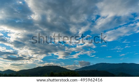 silhouette shot image of mountain and sunset sky in background.