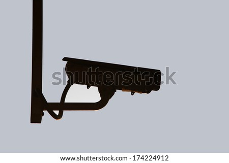 Silhouette shot of hanging CCTV security camera  - stock photo