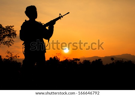 Silhouette shot of soldier holding gun