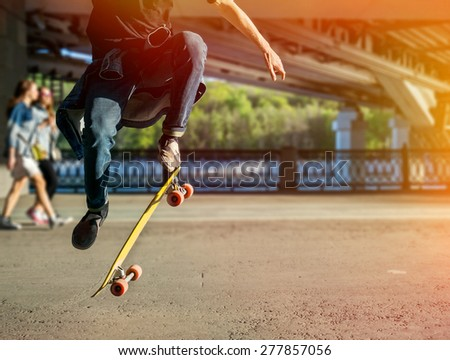 Silhouette skateboarder jumping in city on skateboard under the bridge - stock photo