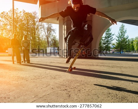 Silhouette skateboarder jumping in city on skateboard under the bridge. In the background two young girls on longboard - stock photo