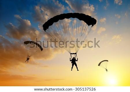 Silhouette skydiver parachutist landing - stock photo