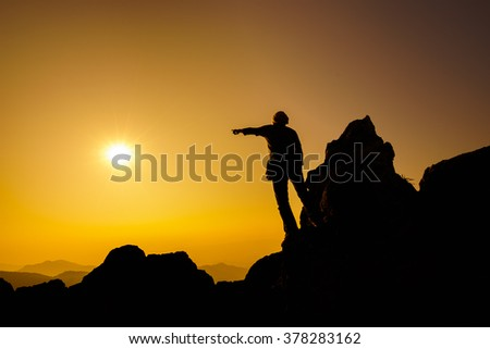 Silhouette Successful concept business man raising arms and stand on top of mountain peak with beautiful sunset landscape. Outdoor leader lifestyle and leadership business success goal concept.