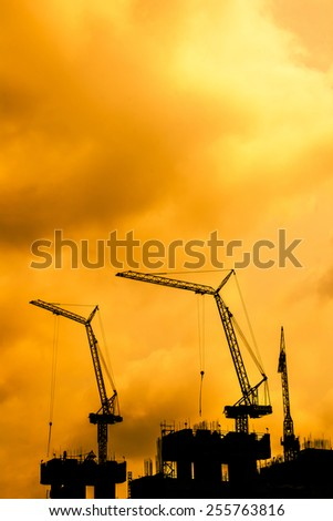 Silhouette three cranes building construction on sunset. Silhouette cranes working. - stock photo