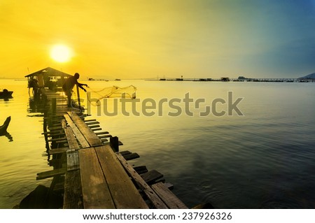 silhouette traditional fishing at ray of sunrise - stock photo