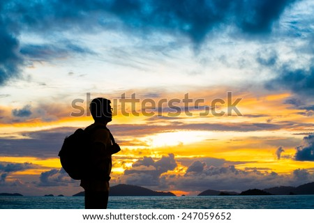 Silhouette traveler with backpack standing near the beach at sunset