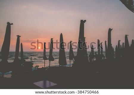 Silhouette umbrella on sunset,vintage,dark tone - stock photo