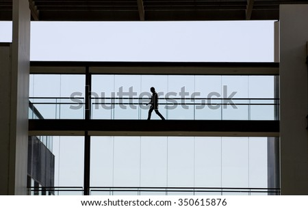 Silhouette view of young businessman in a modern office building interior with panoramic windows. - stock photo