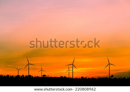 Silhouette wind turbine generator with sunset sky.