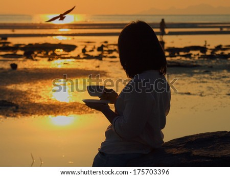 Silhouette woman holding coffee looking at seagull fly over seascape sunset - stock photo