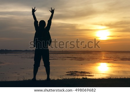 Silhouette woman lifestyle relax at sunset and her raise hands to communicate love
