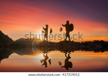 Silhouette woman working for fishing equipment on stone