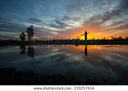 silhouette women and reflection sunset - stock photo