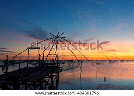 Silhouette wooden bridge and fishing net on lake with morning sunrise in Thailand - stock photo
