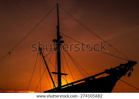 silhouette wooden ship at sunset - stock photo