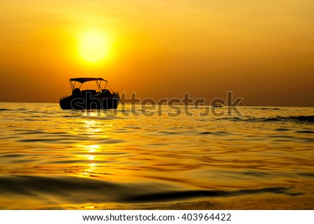 Silhouette yacht in yellow sunset moment - stock photo
