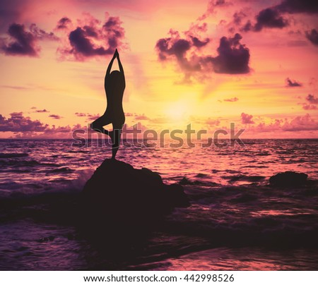 Silhouette yoga woman at sunset beach, vintage filter effect - stock photo