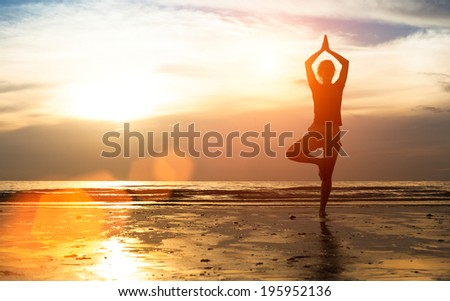 Silhouette young female practicing yoga on the beach at sunset. - stock photo