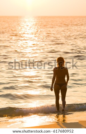 Silhouette young woman on the beach at sunset