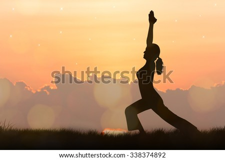 Silhouette young woman practicing yoga at orange sunset background - stock photo