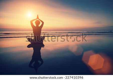 Silhouette young woman practicing yoga on beach at surrealistic sunset.
