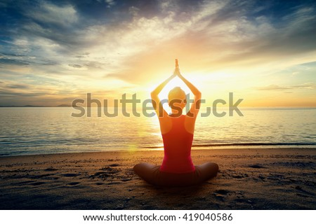 Silhouette young woman practicing yoga on the beach at sunset, Yoga exercise at the beach with sunset