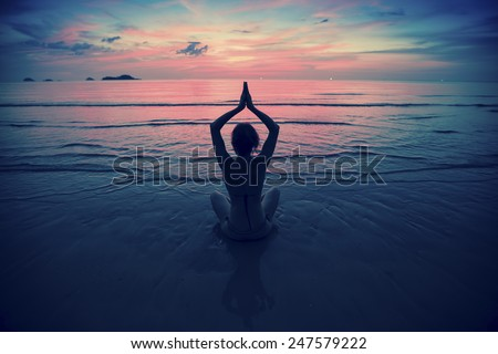 Silhouette young woman practicing yoga on the beach at surrealistic sunset. Yoga and fitness. - stock photo