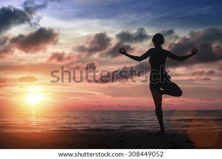 Silhouette young woman practicing yoga on the sea beach at amazing bloody sunset. - stock photo