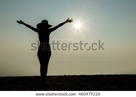Silhouette. Young woman with hat on head enjoy the light sunset on the beach and she feels the freedom. Serene and warm, gentle water.  In front of view opens infinity.