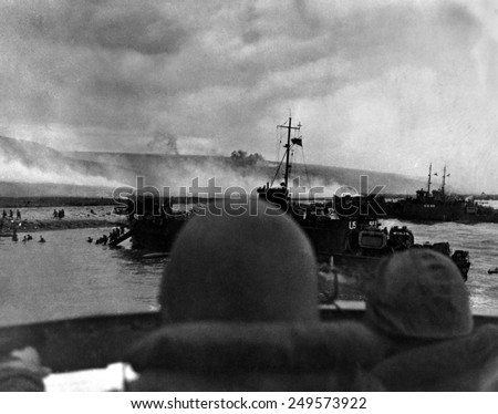 Silhouetted by helmets, view shows two landing craft at Omaha beach on D-Day. Each large ship landed 200 soldiers. June 6, 1944, World War 2. - stock photo