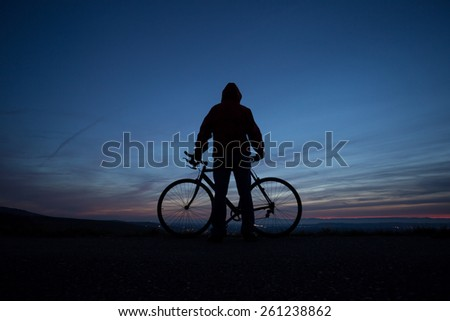 silhouetted cyclist  - stock photo