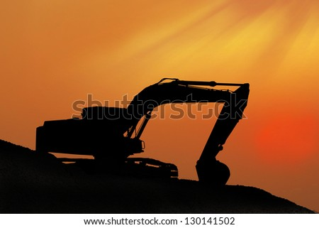 Silhouetted Digging Machine - stock photo