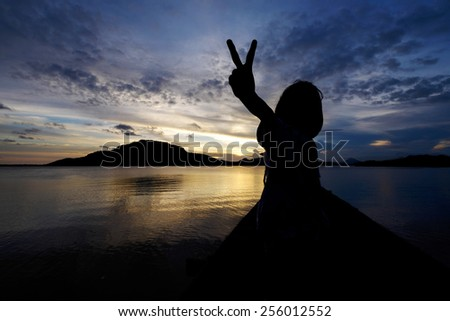 Silhouetted excited and joyous young girl showing peace hand sign with sunset background - stock photo