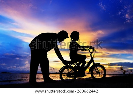 silhouetted Father and his daughter learning to ride a bicycle on the beach at sunset time