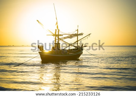 Silhouetted fishing boat in the morning