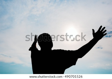 Silhouetted form of a man, looking joyfully to the cheerful, sunny sky with outstretched arms.