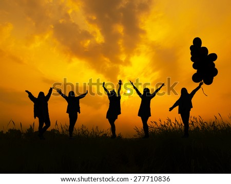 Silhouetted girl holding bunch of air balloons runing at sunset
