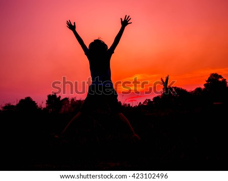 silhouetted girl rope skipping in sunset, Silhouette of happy woman jumping in sunset
