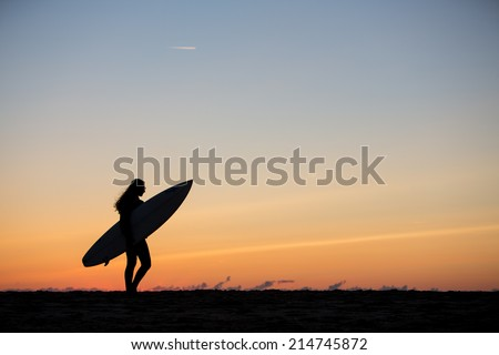 silhouetted girl with surfboard in sunset at beach  - stock photo
