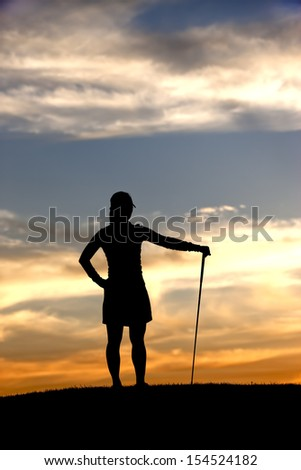 Silhouetted golfer enjoys view. - stock photo