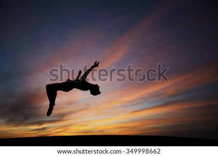 silhouetted gymnast doing backflip in sunset sky - stock photo