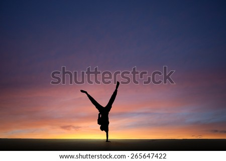 silhouetted gymnast dong one-handed handstand in sunset  - stock photo