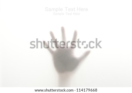 Silhouetted hand on frosted glass
