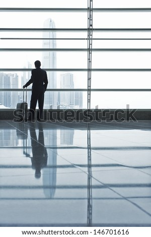 Silhouetted image of businessman with luggage looking through window at airport - stock photo